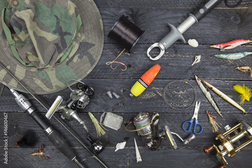 Foto op Aluminium Retro Fishing rods and reels, fishing tackle on black wooden background.