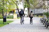 Fototapeta Miasto - Szczęśliwa para, dziewczyna i chłopak jadą na rowerze w parku.