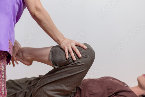 Young woman getting traditional thai stretching massage by asian therapist Fototapete