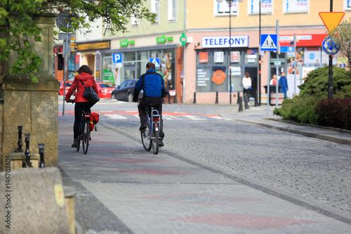 Szczęśliwa para, dziewczyna i chłopak jadą na rowerach przez miasto.