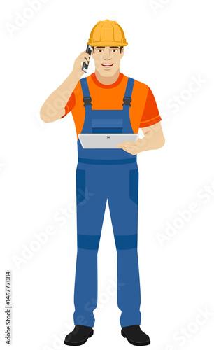 Builder holding digital tablet and talking on the mobile phone Tapéta, Fotótapéta