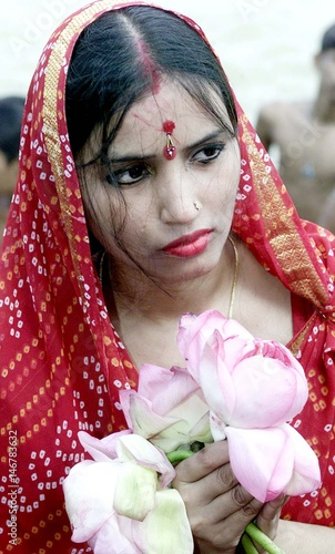 Hindu Woman Holds Lotus Flower While She Prays To Statue Of The