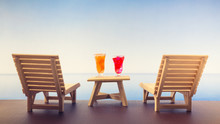 Wooden Beach Chairs Or Sun Loungers With Glass Of Oranges And Strawberry Juices On Balcony And Beautiful Sea View On Clear Day In Summer Season