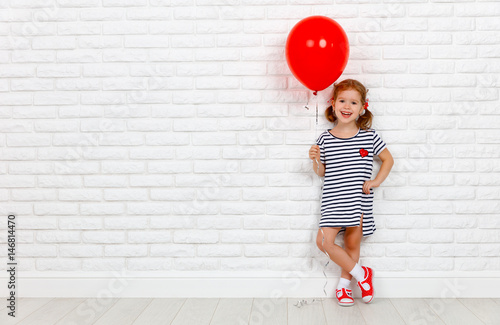 Happy funny child girl with  red ball near an brick wall. фототапет