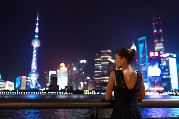 Fototapeta Elegant asian woman in evening dress relaxing by the Bund river in Shanghai looking at the night city lights of Pudong skyline. Luxury travel lifestyle.