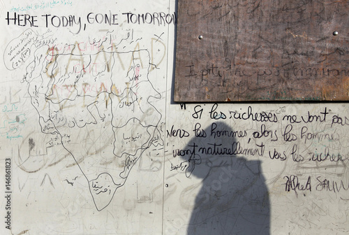 The shadows of an asylum seeker is cast on a wall during a