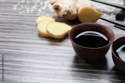 Bowls with tasty soy sauce on wooden background