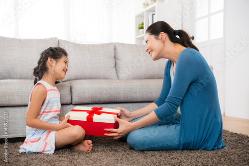 smiling daughter gave her mother a red gift box