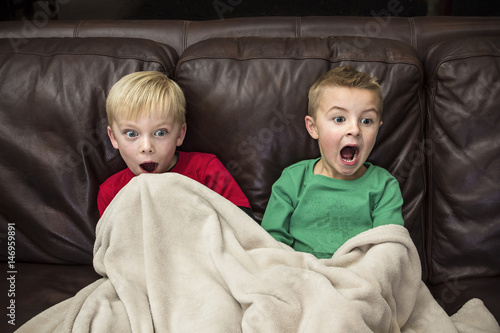 Two scared little boys sitting on the couch watching television together Canvas-taulu
