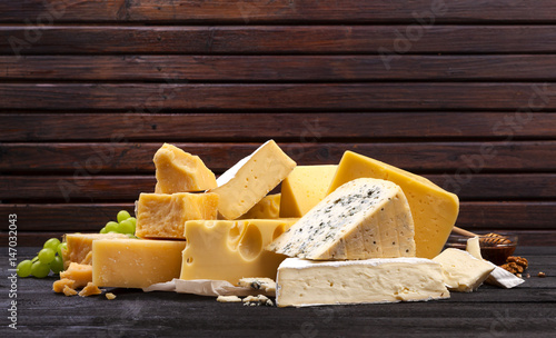 Various types of cheese on black wooden table. Wallpaper Mural
