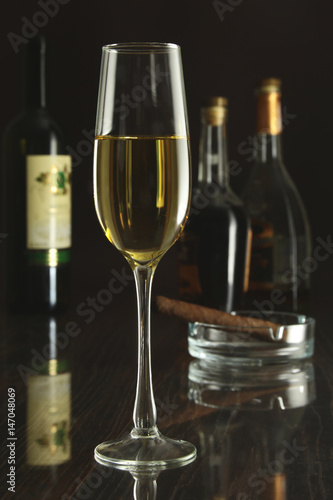 Spoed Foto op Canvas Bar Wine glass and Bottle on a black mirror background