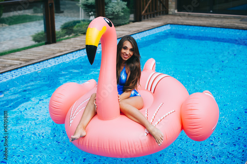 d057c3a9c9e81 Beautiful pregnant woman, wearing swimsuit, lying on a pink flamingo air mattress  in a
