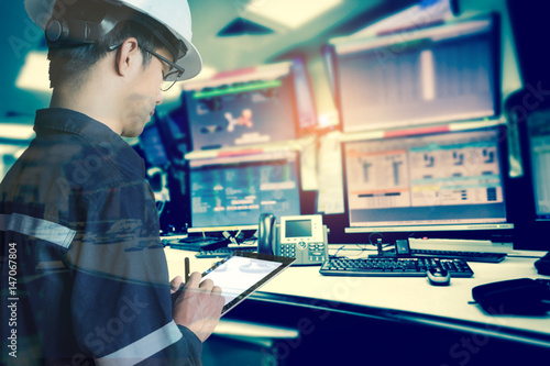 Double exposure of Engineer or Technician man in working shirt working with tablet in control room of oil and gas platform or plant industrial for monitor process, business and industry concept