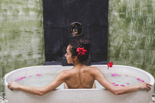Woman relaxing in round outdoor bath with tropical flowers, organic skin care, l Fototapete