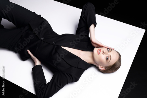 High fashion portrait of young elegant woman in black suit. Canvas