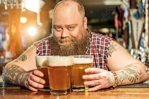 Cheerful bearded man placing glasses of beer Wallpaper Mural