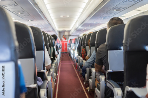 Poster Avion à Moteur passenger seat, Interior of airplane with passengers sitting on seats and stewardess walking the aisle in background. Travel concept,vintage color