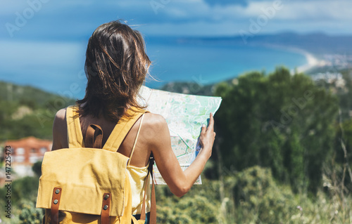 Foto  Hipster tourist hold and look map on trip, lifestyle concept adventure, traveler