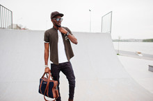 Portrait Of Sitting Stylish African American Man Wear On Sunglasses And Cap With Handbag Outdoor Against Skate Park. Street Fashion Black Man.