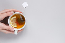 Tea Time. Hands Holding Cup Of Hot Black Tea On The Blue Background, Top View