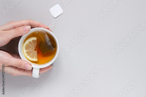 Spoed Fotobehang Thee Tea time. Hands holding cup of hot black tea on the blue background, top view