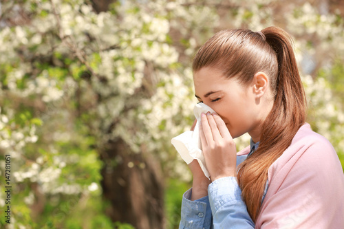 Fotografiet  Sneezing young girl with nose wiper among blooming trees in park