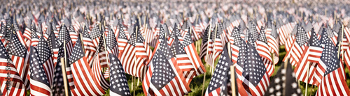 Memorial Day tribute. Thousands of tiny flags in a field. Faded vintage color. Banner format