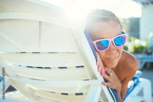 Fotografie, Tablou Woman lying on sunbed