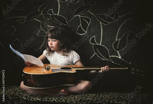 mala-dziewczynka-z-gitara-i-notatkami-na-ciemnym-tle
