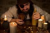 Pirat mit Rum und vielen Kerzen am Tisch, Konzept Mittelalter und Mottoparty