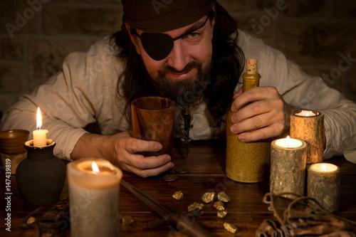Fotografia, Obraz Pirat mit Rum und vielen Kerzen am Tisch, Konzept Mittelalter und Mottoparty