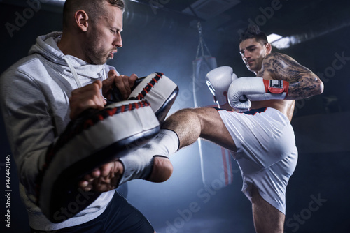 Canvas Print Young athlete doing self defense training .