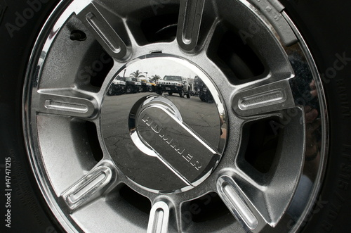 The wheel of a General Motors H2 Hummer reflects other Hummer trucks