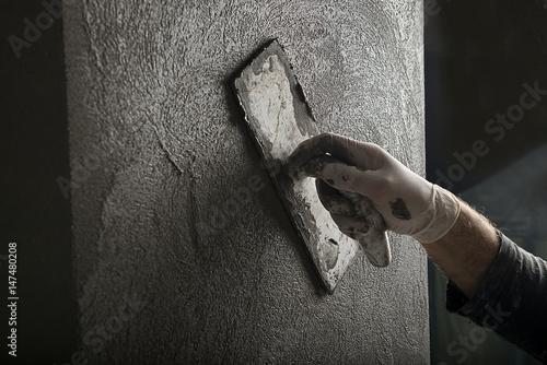 Fotomural  Hand of a construction worker plastering and smoothing concrete wall close-up