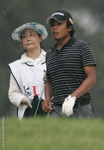 Juvic Pagunsan of the Philippines watches the ball with his caddy at