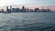 Downtown Miami seen from a boat navigating fast at the sunset.