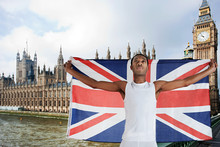 Olympic Competitor With Union Jack In Front Of Houses Of Parliament, London, England
