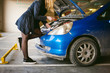woman near car's hood. young blonde in covered parking of shopping center, stands near car with engine compartment bonnet raised, solves problem with engine malfunction, using carabiner wrench tool