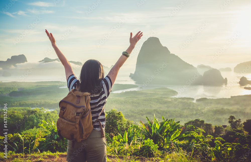 Fototapety, obrazy: Happy young traveler woman backpacker raised arm up to sky enjoying a beautiful of nature at top of mountain and sea view,Freedom wanderlust concept