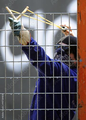 A former shipyard worker wearing a mask uses a slingshot to