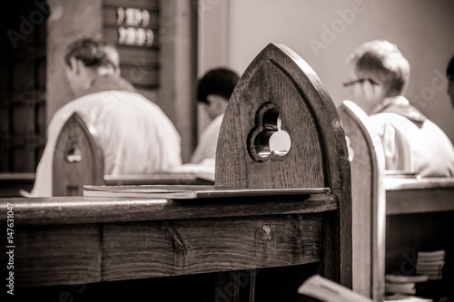 Gothic church pews with priests in the background out of focus Wallpaper Mural