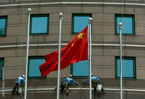 Chinese Workers Clean Wall Outside Building In Downtown Shanghai