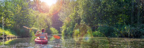 Girl in a kayak and sunny weather, panorama