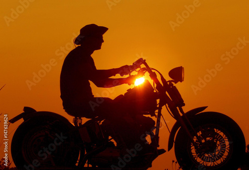 Αφίσα A departing biker rides his old fashion Harley Davidson past a spectacular sunset on the last evenin