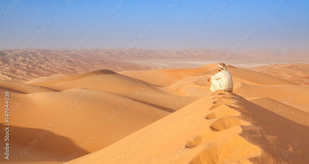 Fototapeta arab man in traditional outfit sitting over a Dune in arabian desert and enjoying the peaceful landscape of the empty quarter