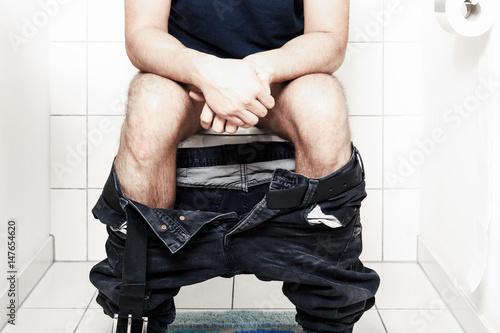 Photo  Man sitting on the toilet