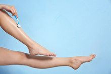 Beautiful Young Woman Shaving Legs On Color Background