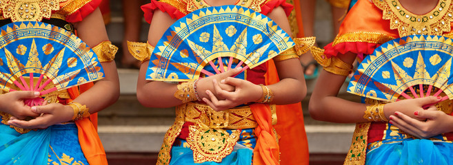 Asian travel background. Group of beautiful Balinese dancer women in traditional Sarong costumes with fans in hands dancing Legong dance. Arts, culture of Indonesian people, Bali island festivals.