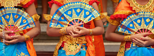 Poster Indonésie Asian travel background. Group of beautiful Balinese dancer women in traditional Sarong costumes with fans in hands dancing Legong dance. Arts, culture of Indonesian people, Bali island festivals.