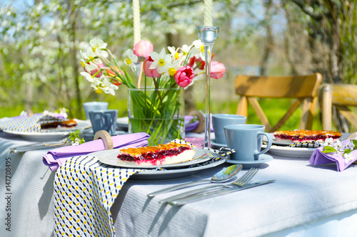 Deurstickers Picknick Table setting and cage with flowers in garden